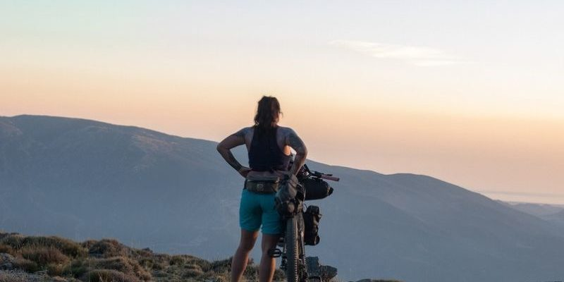 woman bikepacker on a mountain peak at dusk